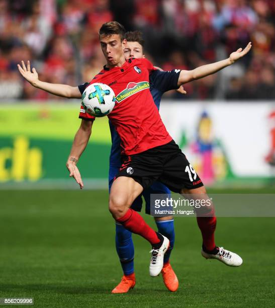 Janik Haberer of SC Freiburg is challenged by Dennis Geiger of 1899 Hoffenheim during the Bundesliga match between SportClub Freiburg and TSG 1899...