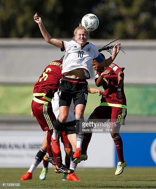 Janina Minge of Germany jumps for a header with Gladysmar Rojas and Dayana Rodriguez of Venezuela during the FIFA U17 Women's World Cup Group B match...