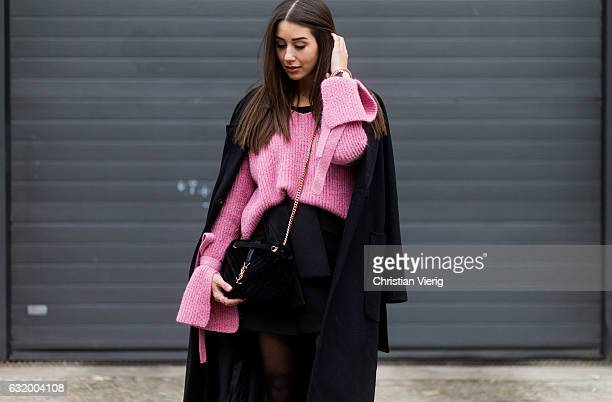Janina Pfau wearing a Zara mini skirt tights Balenciaga boots YSL bag a pink Mango knit with wide sleeves a black Edited coat during the MercedesBenz...