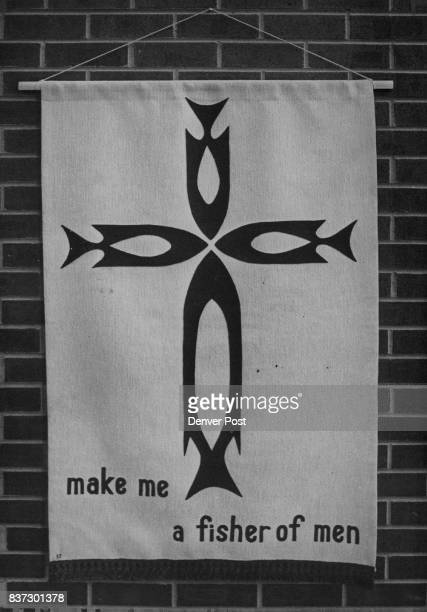 Janis Shubert incorporates stylized fish designs in the form of a crucifix in her cloth collage banner in blue and white Credit Denver Post