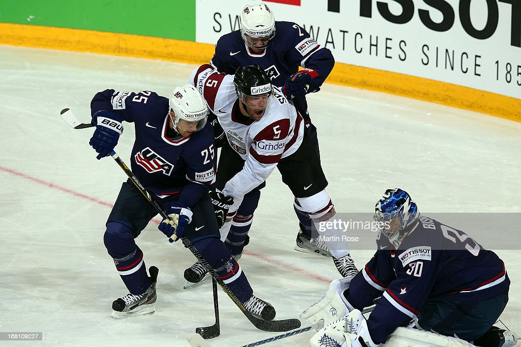 Janis Sprukts (C) of Latvia and Matt Carle (#25) and Jeff Perty (#2) of USA battle for the puck during the IIHF World Championship group H match between Latvia and USA at Hartwall Areena on May 5, 2013 in Helsinki, Finland.