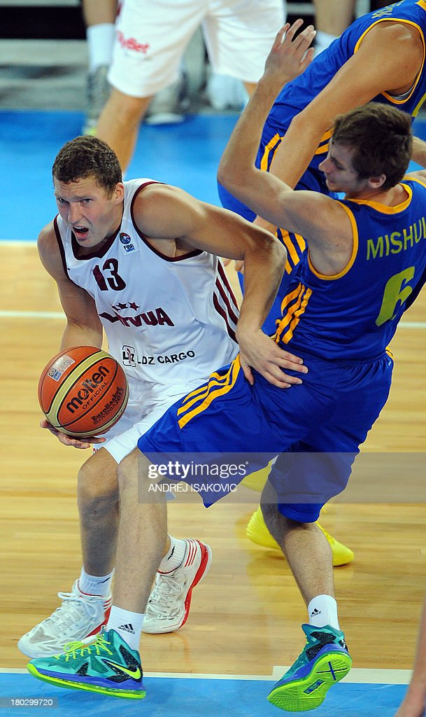 Janis Strelnieks of Latvia (L) vies with Olexandr Mishula of Ukraine during their FIBA Eurobasket second round Group E qualification match between Latvia and Ukraine at the Stozice Arena in Ljubljana, on September 11, 2013.