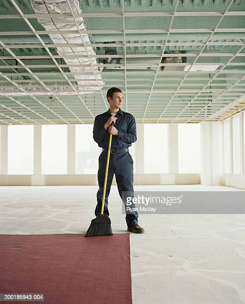 Janitor holding broom in empty office space