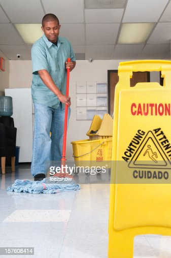 A janitor in a blue uniform mopping a floor in an office
