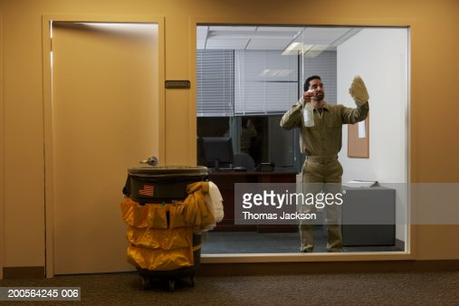Janitor in office late at night, cleaning window