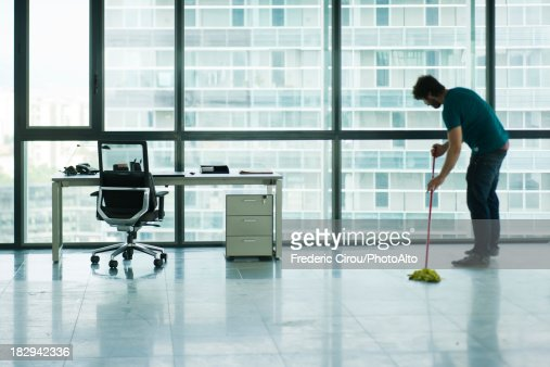 Janitor mopping empty office