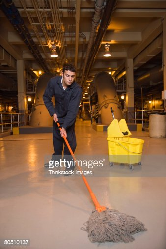 Janitor mopping floor in waste treatment plant