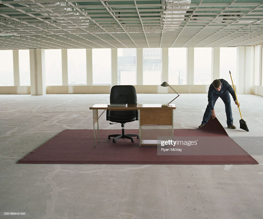 Janitor Sweeping Dust Under Rug In Office Space : Stock Photo