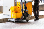 Janitorial and mop bucket on cleaning in process and worker on work.