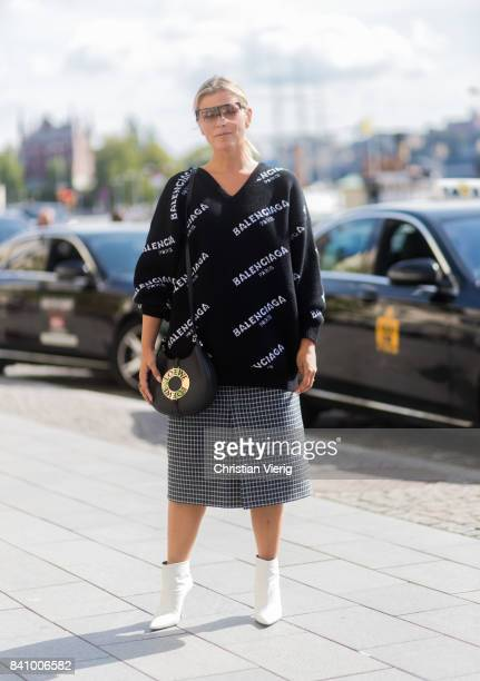 Janka Polliani wearing black Balenciaga sweater Loewe bag checked skirt outside Whyred on August 30 2017 in Stockholm Sweden