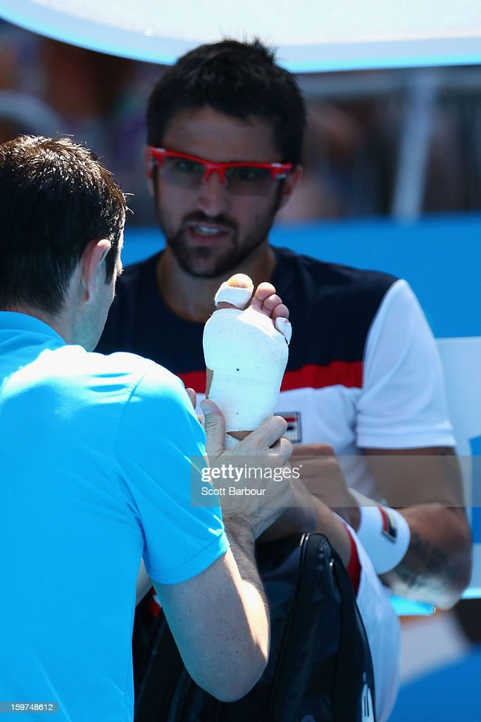 Janko Tipsarevic of Serbia has his foot looked at by a trainer in his fourth round match against Nicolas Almagro of Spain during day seven of the 2013 Australian Open at Melbourne Park on January 20, 2013 in Melbourne, Australia.