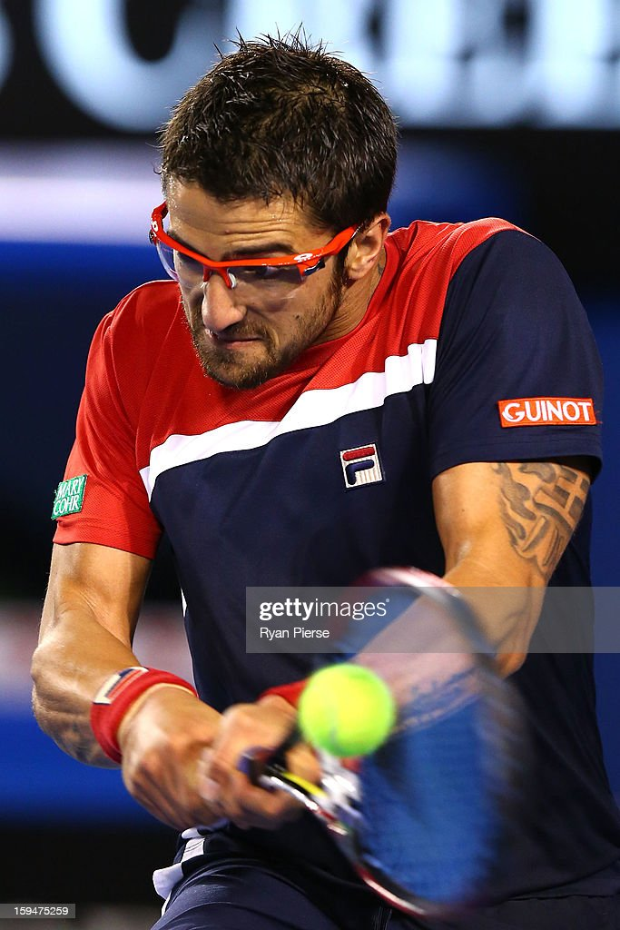 Janko Tipsarevic of Serbia plays a backhand in his first round match against Lleyton Hewitt of Australia during day one of the 2013 Australian Open at Melbourne Park on January 14, 2013 in Melbourne, Australia.