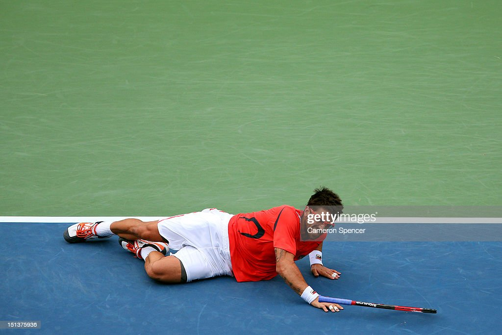 Janko Tipsarevic of Serbia slips on the court against David Ferrer of Spain during their men's singles quarterfinal match on Day Eleven of the 2012 US Open at USTA Billie Jean King National Tennis Center on September 6, 2012 in the Flushing neighborhood of the Queens borough of New York City.