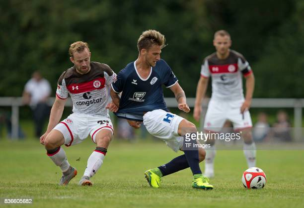 JanMarc Schneider of St Pauli and Alexander Luettmers of Oldenburg battle for the ball during the preseason friendly match between VfB Oldenburg and...