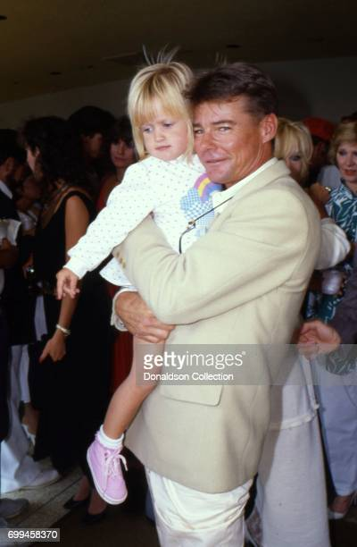 JanMichael Vincent from the cast of the tv show 'Airwolf' poses for a portrait with a little girl in September 1986 in Los Angeles California