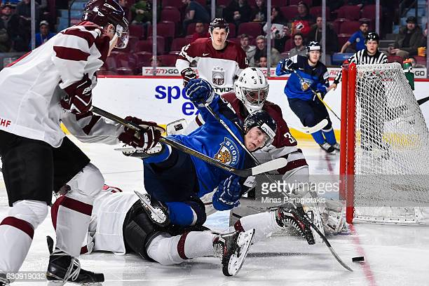 Janne Kuokkanen of Team Finland falls in front of goaltender Mareks Mitens of Team Latvia during the 2017 IIHF World Junior Championship relegation...