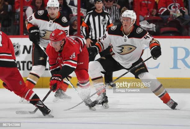Janne Kuokkanen of the Carolina Hurricanes and Josh Manson of the Anaheim Ducks battle for the loose puck during an NHL game on October 29 2017 at...