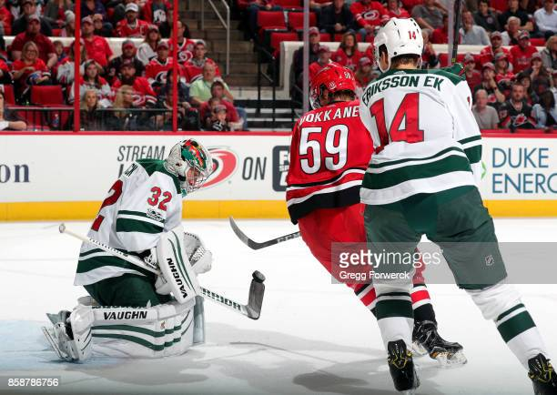 Janne Kuokkanen of the Carolina Hurricanes has his shooting attempt blocked by Alex Stalock of the Minnesota Wild as he is pursued by Joel Eriksson...