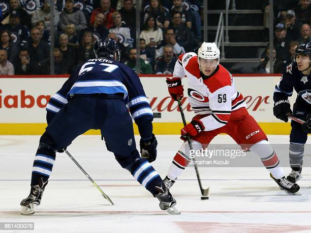 Janne Kuokkanen of the Carolina Hurricanes plays the puck down the ice as Tyler Myers of the Winnipeg Jets defends during first period action at the...