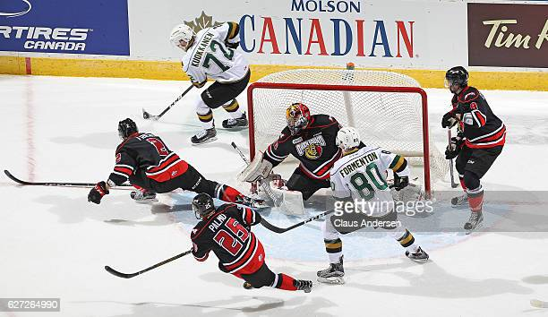 Janne Kuokkanen of the London Knights looks to get a puck out to teammate Alex Formenton against Michael McNiven of the Owen Sound Attack during an...