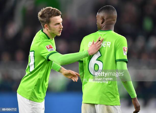 Jannes Horn brushes a bee from the shirt of Riechedly Bazoer of Wolfsburg during the Bundesliga match between VfL Wolfsburg and SC Freiburg at...