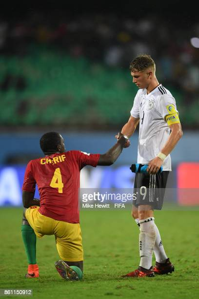 JannFiete Arp of Germany helps Cherif Camara of Guinea to his feet at the end of the FIFA U17 World Cup India 2017 group C match between Guinea and...