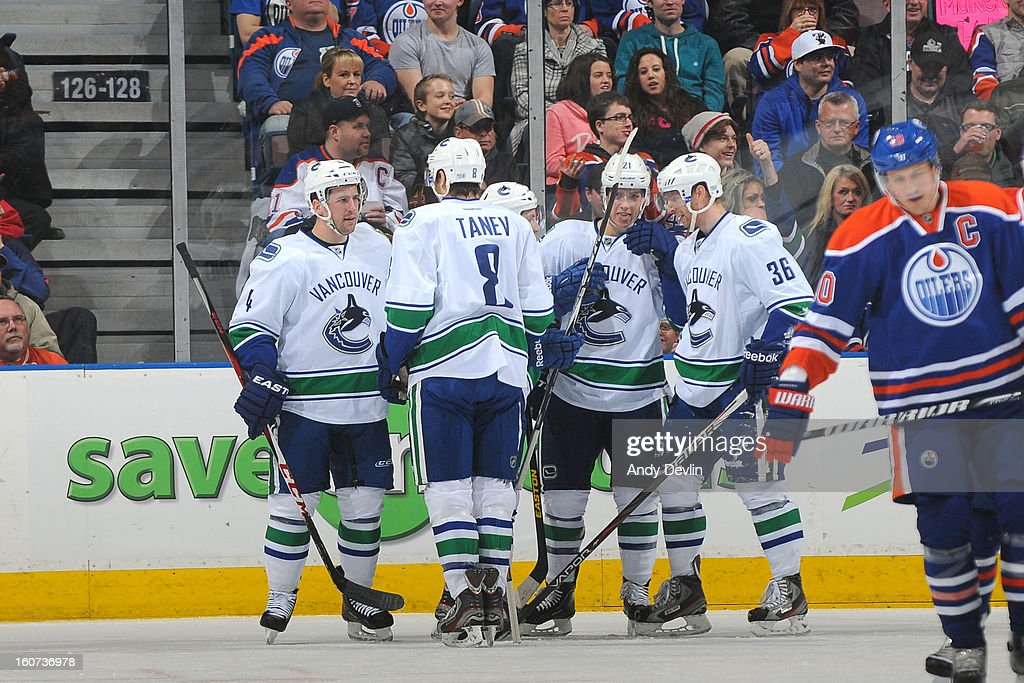 Jannik Hansen #36, Keith Ballard #4 and Chris Tanev #8 of the Vancouver Canucks celebrate with team mates after scoring a goal inan NHL game against theEdmonton Oilers on February 4, 2013 at Rexall Place in Edmonton, Alberta, Canada.