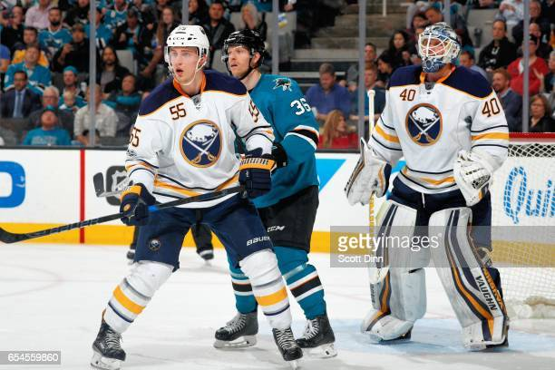 Jannik Hansen of the San Jose Sharks along with Rasmus Ristolainen and Robin Lehner of the Buffalo Sabres look on during a NHL game at SAP Center at...