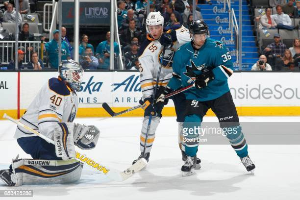Jannik Hansen of the San Jose Sharks is defended by Robin Lehner and Rasmus Ristolainen of the Buffalo Sabres at SAP Center at San Jose on March 14...