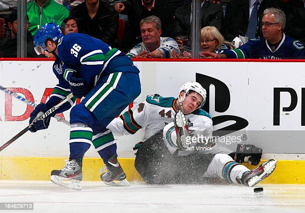 Jannik Hansen of the Vancouver Canucks checks MarcEdouard Vlasic of the San Jose Sharks to the ice during their NHL game at Rogers Arena March 5 2013...