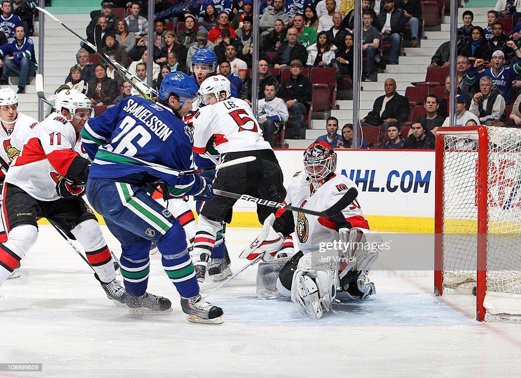 Jannik Hansen of the Vancouver Canucks scores on Brian Elliott of the Ottawa Senators while Daniel Alfredsson of the Ottawa Senators and Ryan Kesler...