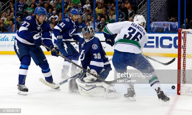 Jannik Hansen of the Vancouver Canucks scores past goal Ben Bishop and defenders Victor Hedman and Valtteri Filppula of the Tampa Bay Lightning at...