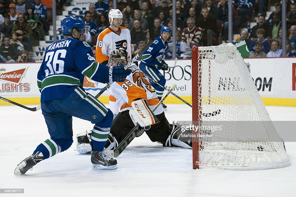 Jannik Hansen #36 of the Vancouver Canucks scores the second goal during the second period on Steve Mason #35 of the Philadelphia Flyers on December 30, 2013 at Rogers Arena in Vancouver, British Columbia, Canada.