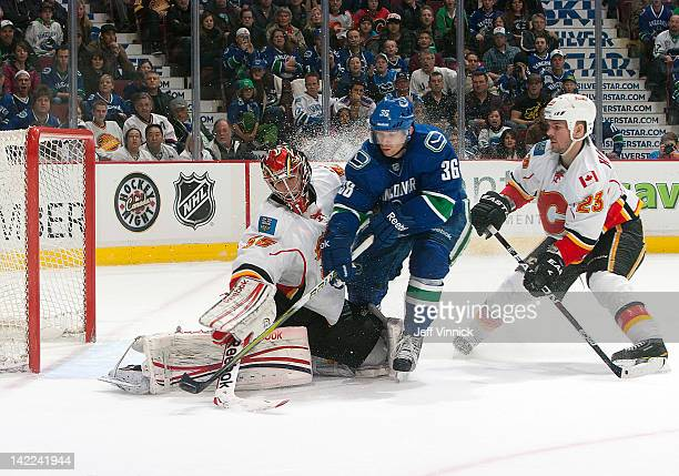 Jannik Hansen of the Vancouver Canucks squeezed between Henrik Karlsson and Scott Hannan of the Calgary Flames during their NHL game at Rogers Arena...