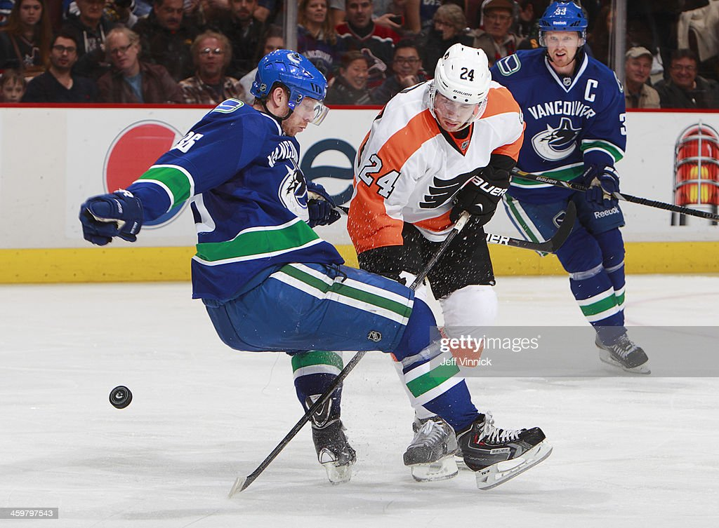Jannik Hansen #36 of the Vancouver Canucks trips while being checked by Matt Read #24 of the Philadelphia Flyers during an NHL game at Rogers Arena December 30, 2013 in Vancouver, British Columbia, Canada. Philadelphia won 4-3.