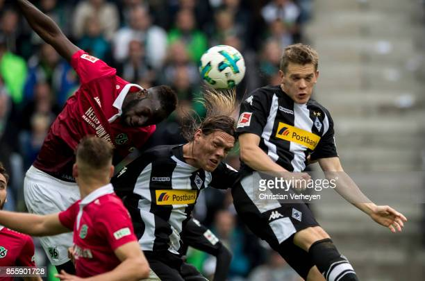 Jannik Vestergaard and Matthias Ginter of Borussia Moenchengladbach and Salif Sane of Hannover 96 battle for the ball during the Bundesliga match...