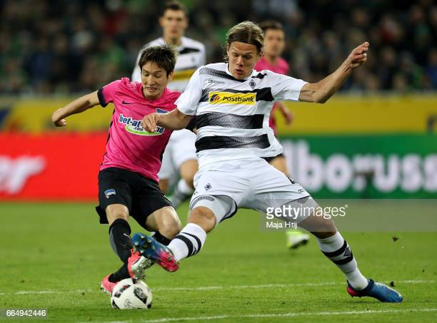Jannik Vestergaard of Gladbach and Genko Haraguchi of Berlin battle for the ball during the Bundesliga match between Borussia Moenchengladbach and...