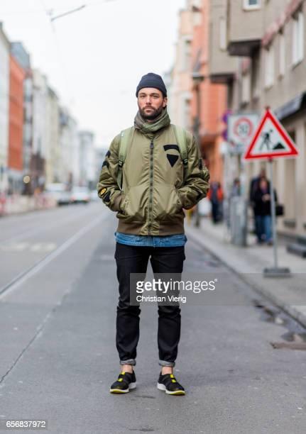 Janosch wearing an olive green bomber jacket beanie sneaker denim jeans backpack on March 22 2017 in Berlin Germany
