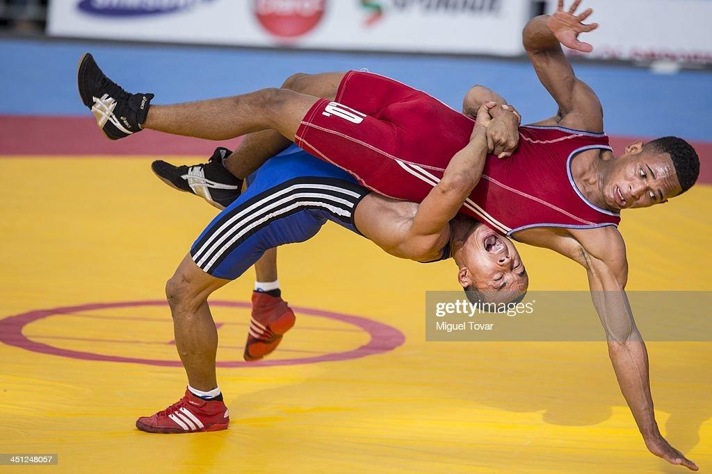 Jansel Gonzalez of Dominican Republic competes with Jairo Medina of Venezuela in Wrestling 55 kg event as part of the XVII Bolivarian Games Trujillo 2013 at Huaca del Sol complex on November 21, 2013 in Trujillo, Peru.