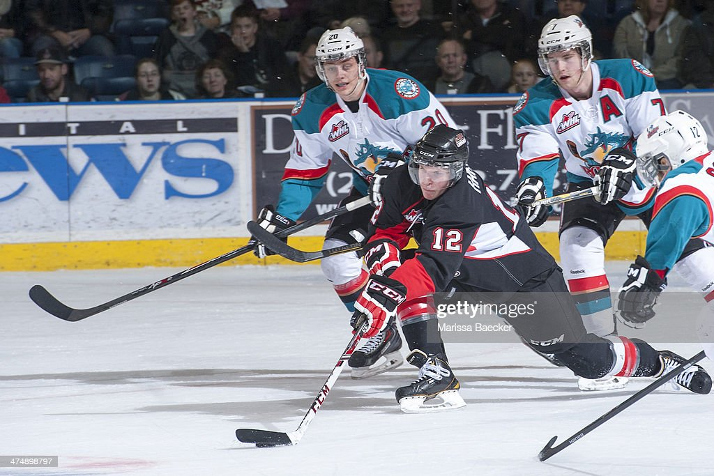 Jansen Harkins #12 of the Prince George Cougars is checked during first period by Austin Glover #20 and Damon Severson #7 of the Kelowna Rockets on February 25, 2014 at Prospera Place in Kelowna, British Columbia, Canada.