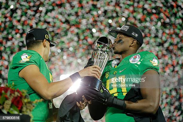 Oregon Ducks linebacker Tony Washington kisses The Leishman Trophy after the College Football Playoff Semifinal Rose Bowl Game presented by...
