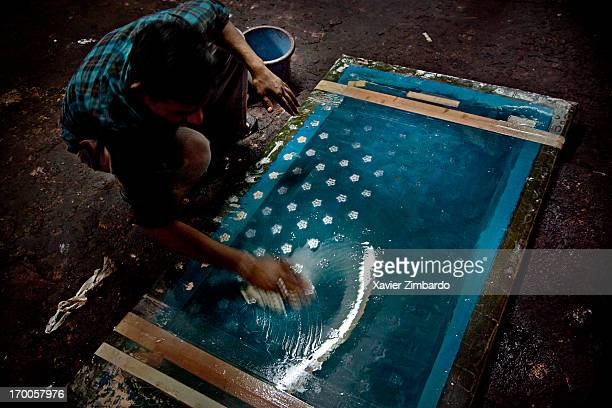 A worker washes a fabric printing screen on January 13 2012 in a dyeing factory in Rajasthan India A fabric printing screen is mounted on a printing...