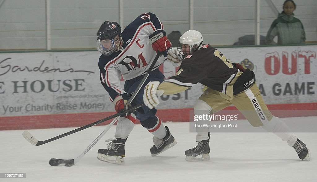 DeMatha C Garrett Hasken (24) gains control of the puck against Landon D John Barton on January 18, 2013 in Laurel, MD
