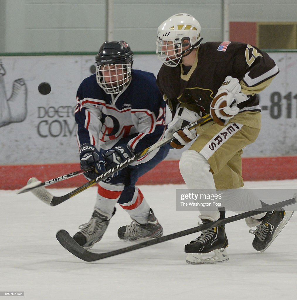 DeMatha F Sean Watson (25) (L) and Landon F Michael Soraci (22) battle for a loose puck on January 18, 2013 in Laurel, MD