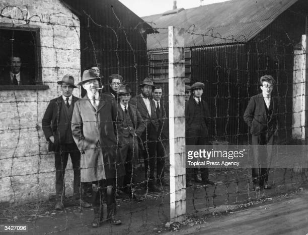 Imprisoned members of Sinn Fein behind barbed wire during an inspection of the Royal Irish Constabulary by Sir Hamar Greenwood