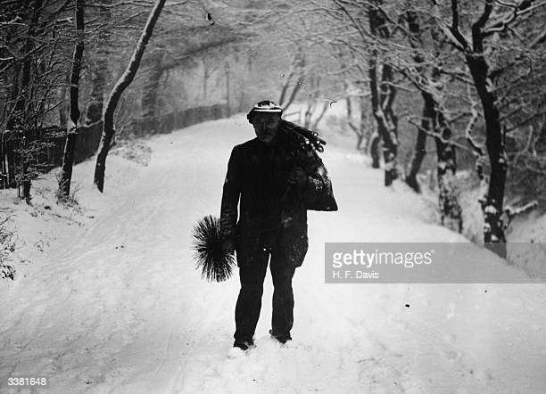 A chimney sweep walking to work in rural Essex through heavy snow with his equipment