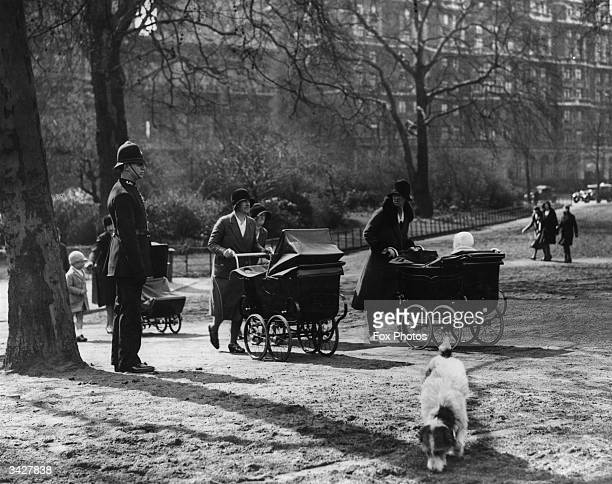 Nursemaids pushing prams in Hyde Park under the watchful eye of a policeman