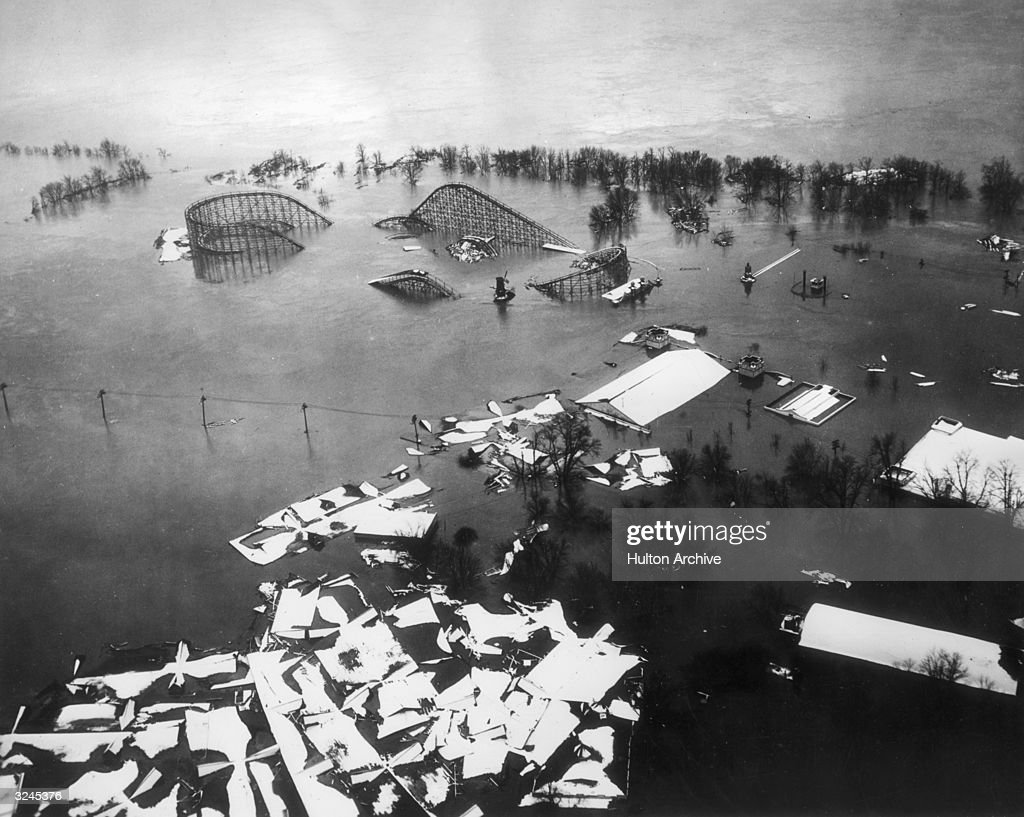 Aerial view of a rollercoaster partly submerged under water with building wreckage floating on the surface after the Ohio River flood Coney Island...