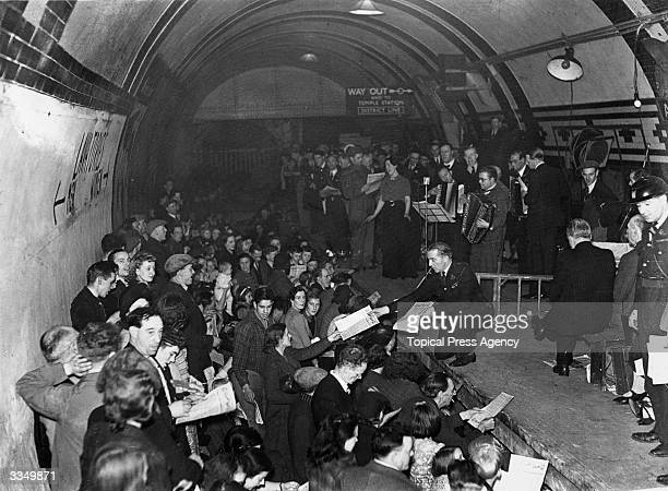 A man handing out information to the members of the audience during a concert given by ENSA at Aldwych underground station London The audience is...