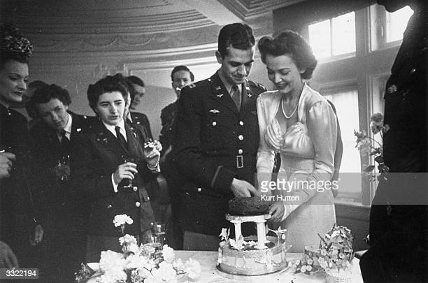 American film actress Carole Landis cutting a sultana cake disguised as a wedding cake with her husband American Airforce captain Thomas Wallace at...